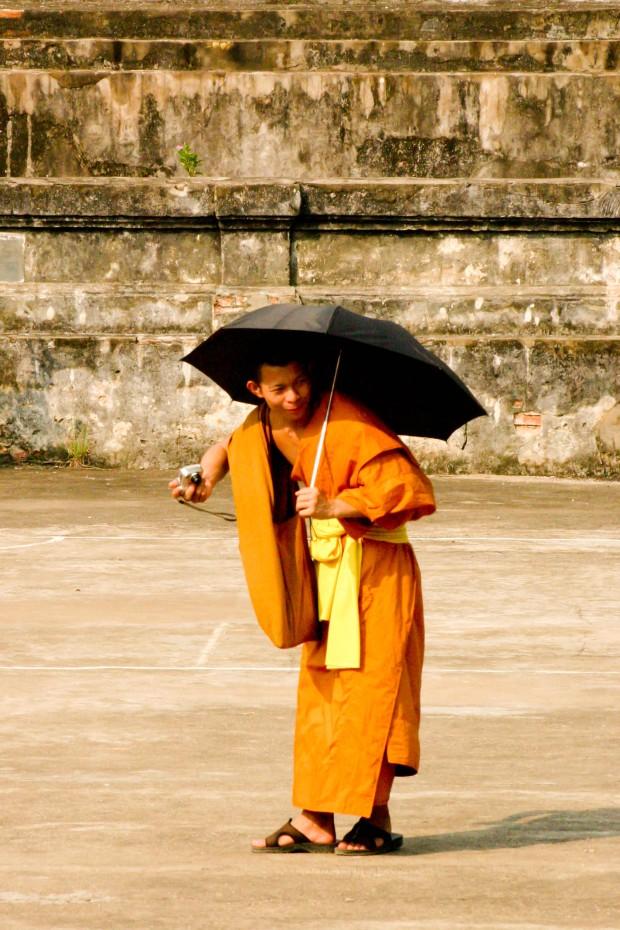 Laos 2008. Le moine photographe, dans une main son instamatic, dans l'autre son parapluie qui lui sert de parasol. Les Laotiens aiment avoir la peau blanche et par conséquent, se protègent du soleil.