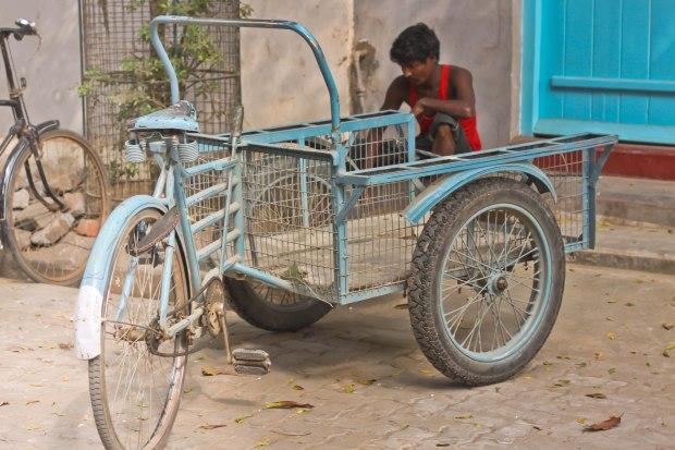 Le vélo, carriole de transport, de même couleur que la porte de la maison.Le conducteur attend patiemment de pouvoir travailler.