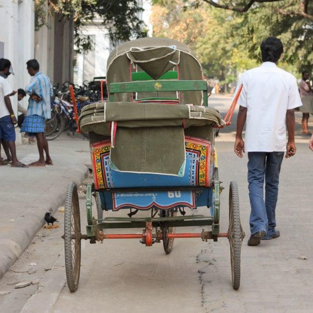 Un cyclo-pousse vide dont le conducteur attend un hypothétique client pour un travail éreintant.