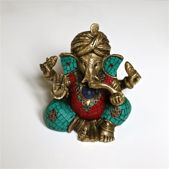 Turban Ganesh à 4 bras . Il porte un fruit que sa trompe ouverte vient goûter.